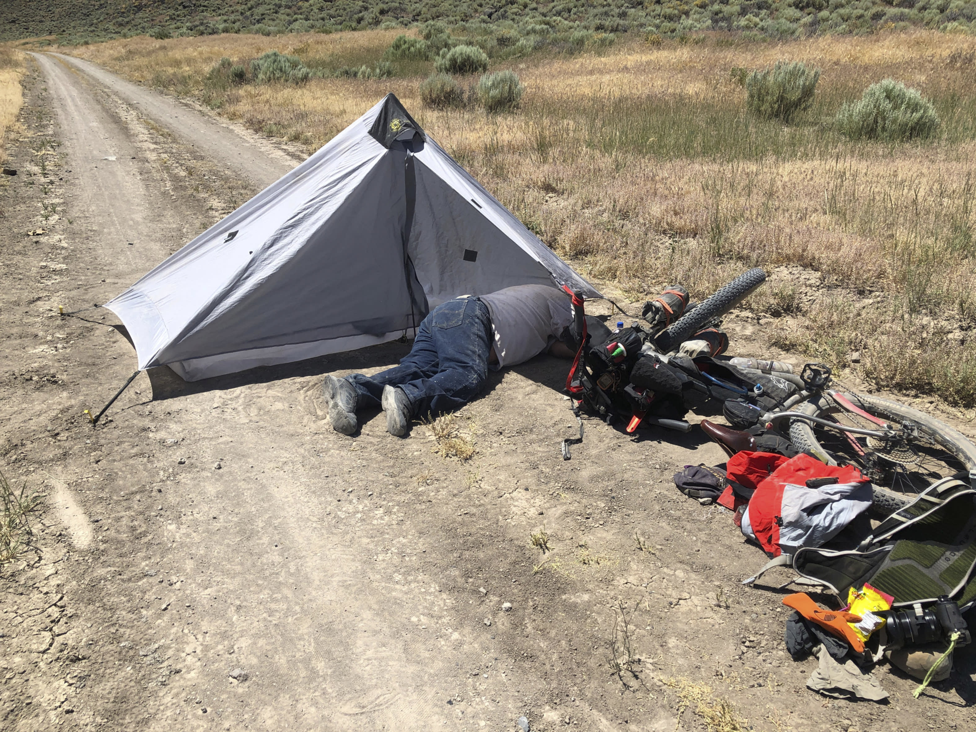 This July 18, 2019, photo provided by Tomas Quinones shows Gregory Randolph, a 73-year-old man who was stranded in the remote Oregon high desert. The 73-year-old man who was stranded in the remote Oregon high desert for four days with his two dogs was rescued when a long-distance mountain biker discovered him near death on a dirt road, authorities said Thursday, July 25. (Tomas Quinones via AP)