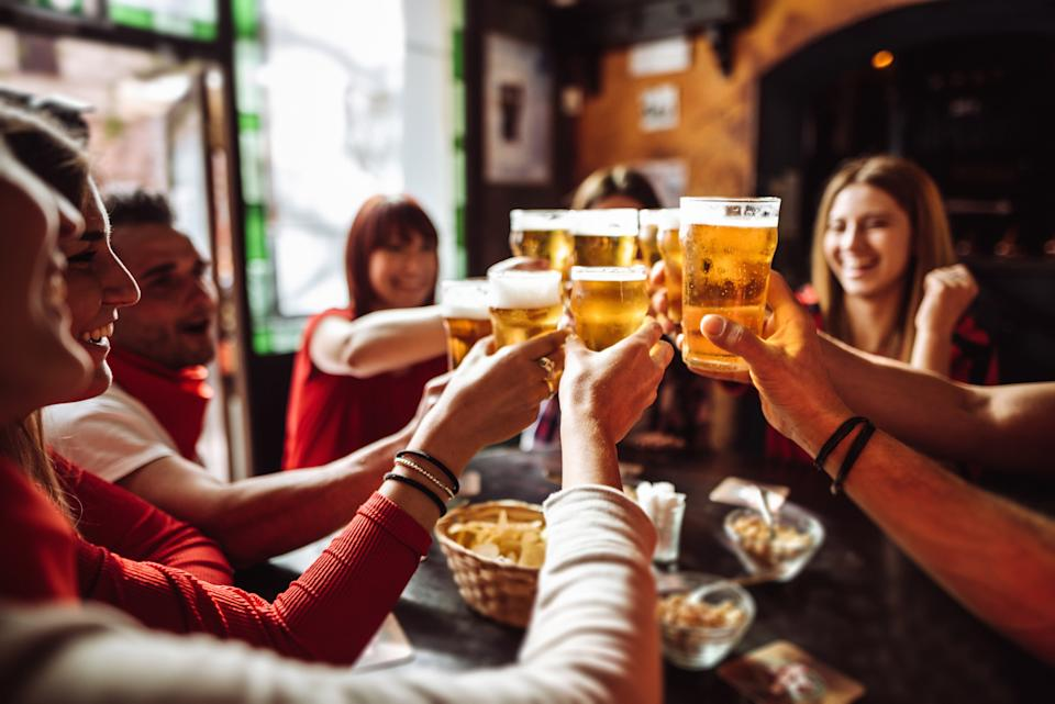 People cheers with their beers inside a pub.