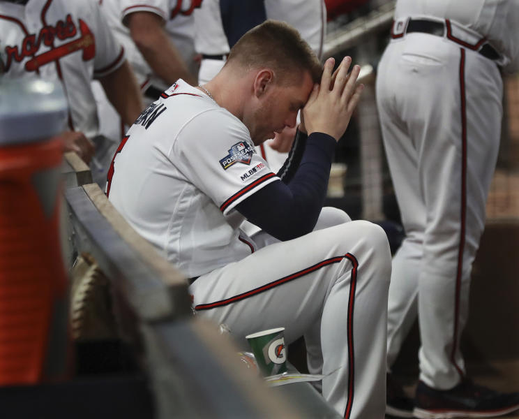Atlanta Braves first baseman Freddie Freeman sits in the dugout during the ninth inning of the team's 13-1 loss to the St. Louis Cardinals during Game 5 of a baseball National League Division Series on Wednesday, Oct. 9, 2019, in Atlanta. (Curtis Compton/Atlanta Journal-Constitution via AP)