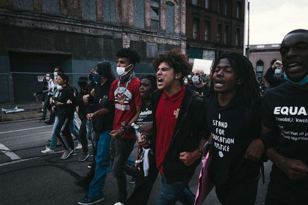 PHOTO: Stefan Perez locks arms with other protesters while marching down a Detroit street. (Courtesy Diego Cruz)