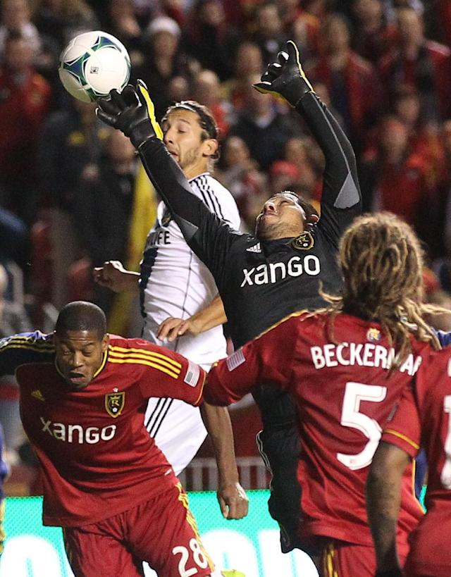 Real Salt Lake goalie Nick Rimando makes a save while Los Angeles Galaxy's Omar Gonzalez, rear, looks on as Real Salt Lake defender Chris Schuler (28) and Kyle Beckerman (5) defend in the first half during the second leg of the MLS Western Conference semifinal soccer game, Thursday, Nov. 7, 2013, in Sandy, Utah. (AP Photo/Rick Bowmer)