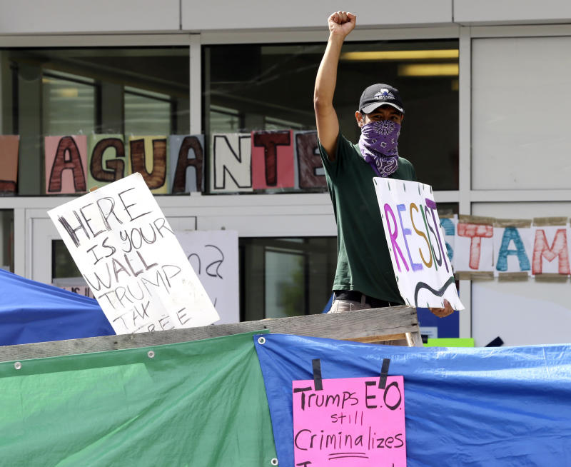 An unidentified man holds a sign behind a makeshift wall in a protest camp a property in front of the US Immigration and Customs Authority in Portland, Ore.