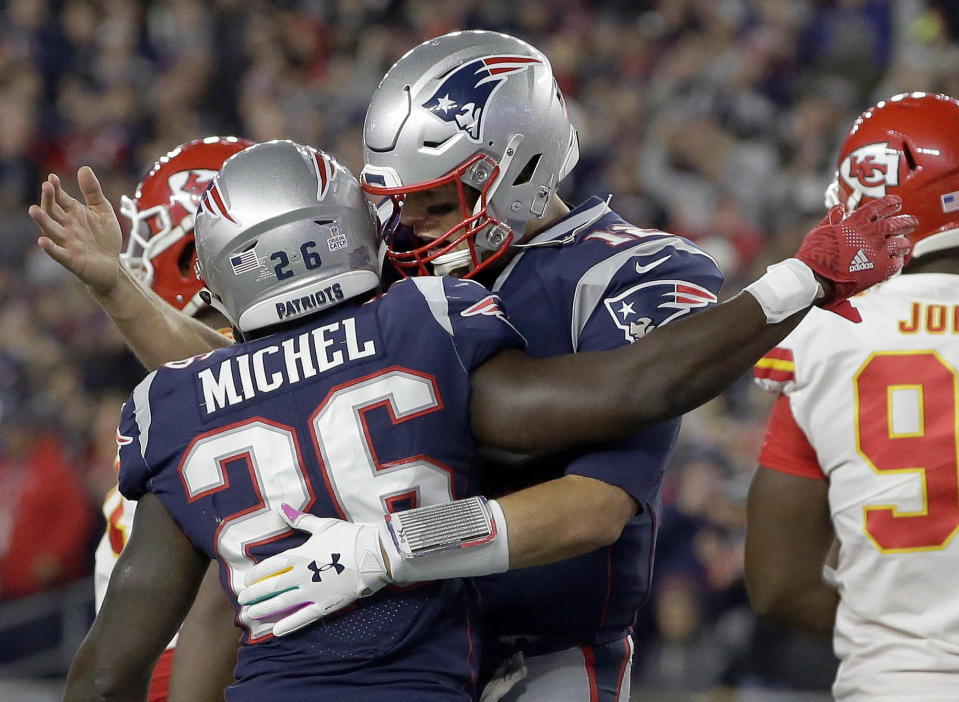 New England Patriots quarterback Tom Brady, right, celebrates a rushing touchdown by running back Sony Michel (26) during the first half of an NFL football game against the Kansas City Chiefs, Sunday, Oct. 14, 2018, in Foxborough, Mass. (AP Photo/Steven Senne)