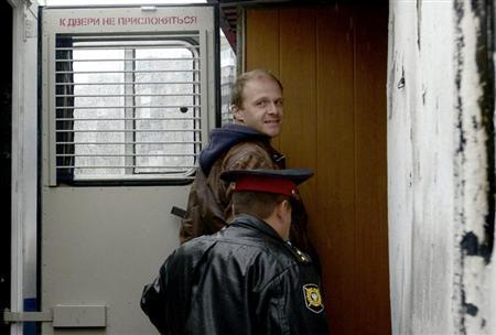 Photographer Denis Sinyakov, one of the 30 people detained after a Greenpeace protest at the Prirazlomnaya platform, is escorted to a district court building in Murmansk, September 26, 2013. REUTERS/Stringer