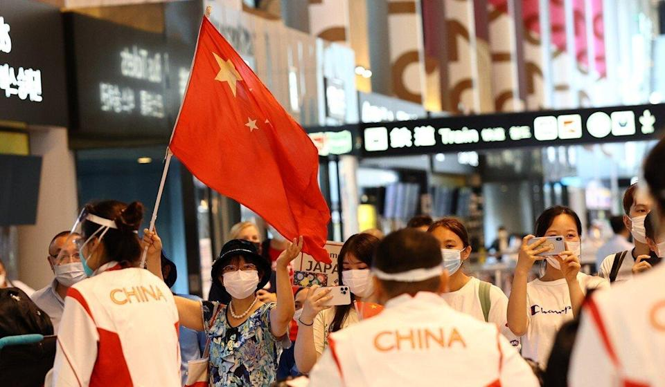 A supporter greets members of the China delegation on their arrival in Tokyo ahead of the Olympic Games. Photo: Reuters
