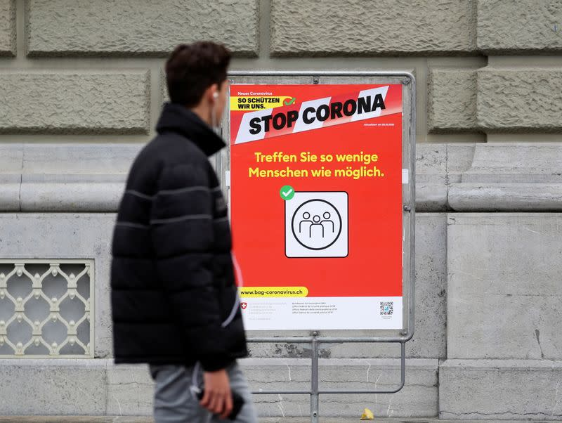 """A poster reading """"How we protect ourselves. Stop Corona. Meet less people as possible"""" is pictured in front of the Bundeshaus in Bern"""