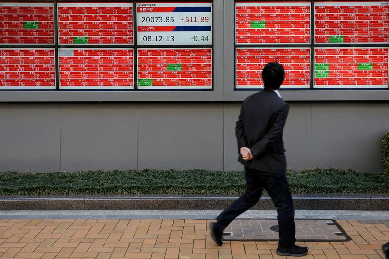 FILE PHOTO: A man looks at an electronic board showing the Nikkei stock index outside a brokerage in Tokyo