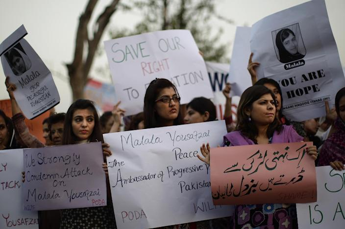 "Pakistani women, hold banners during a protest condemning the attack on schoolgirl Malala Yousufzai, in Islamabad, Pakistan, Wednesday, Oct. 10, 2012. Pakistani doctors successfully removed a bullet Wednesday from the neck of a 14-year-old girl who was shot by the Taliban for speaking out in support of education for women, a government minister said. Banner bottom right reads, "" The Taliban is afraid of an unarmed girl."" (AP Photo/Muhammed Muheisen)"