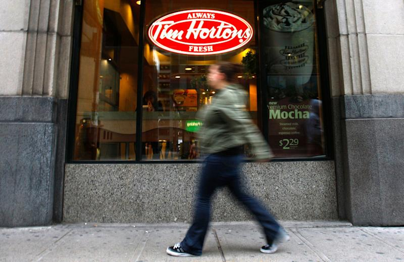 A pedestrian walks past a Tim Hortons restaurant in Toronto October 26, 2007. Profit at Tim Hortons Inc jumped 30 percent in the third quarter, the coffee and doughnut chain said, crediting higher prices, lower taxes and big sales growth. REUTERS/Mark Blinch (CANADA)