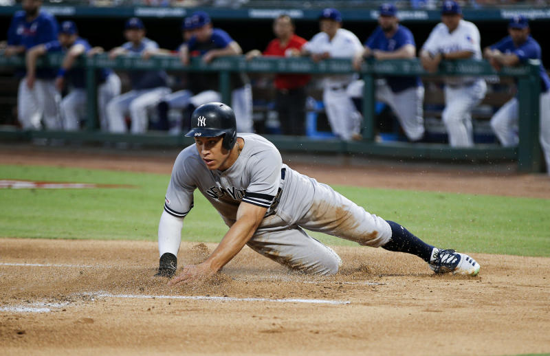 New York Yankees' Aaron Judge (99) slides into home on a sacrifice fly RBI hit by Brett Gardner during the first inning of a baseball game against the Texas Rangers, Saturday, Sept. 28, 2019, in Arlington, Texas. (AP Photo/Brandon Wade)