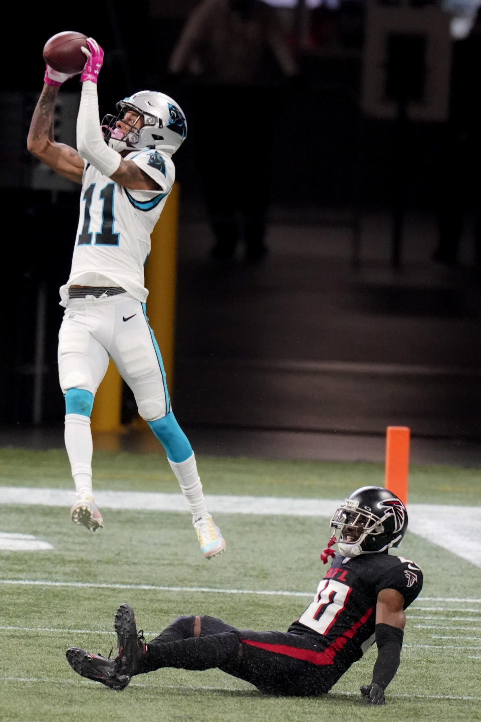 Carolina Panthers wide receiver Robby Anderson (11) makes the catch over Atlanta Falcons defensive back Kendall Sheffield (20) during the first half of an NFL football game, Sunday, Oct. 11, 2020, in Atlanta. Sheffield was injured on the play. (AP Photo/Brynn Anderson)
