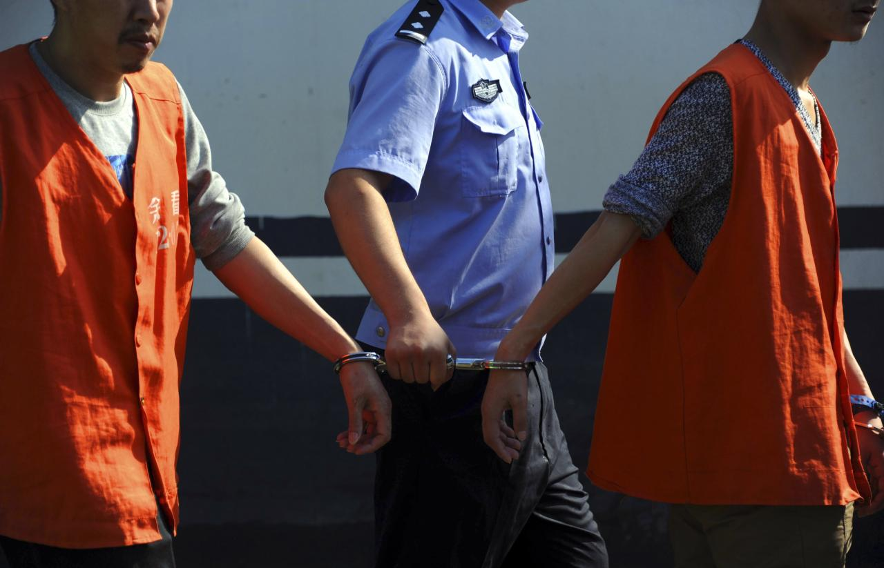 A police officer holds the handcuffs cuffing two inmates during a relocation of inmates at a flooded detention house in Yuyao