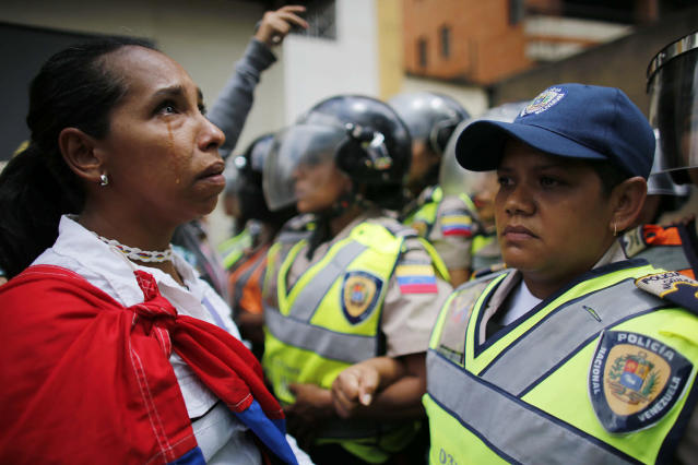 <p>A demonstrator stands in front of policewomen blocking an opposition march from reaching the Interior Ministry in Caracas, Venezuela, May 6, 2017. Thousands of women wearing white and carrying flowers marched to ask for a stop of repression and to pay tribute to those who were killed in weeks of near-daily violent protests calling on President Nicolas Maduro to step down. (Photo: Ariana Cubillos/AP) </p>
