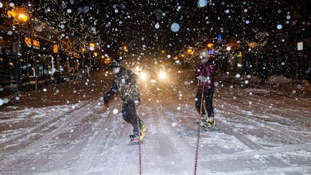 PHOTO: Snowboarders ride behind an SUV as snow continues to fall on Dec. 23, 2020, in Minneapolis. (Stephen Maturen/Getty Images)