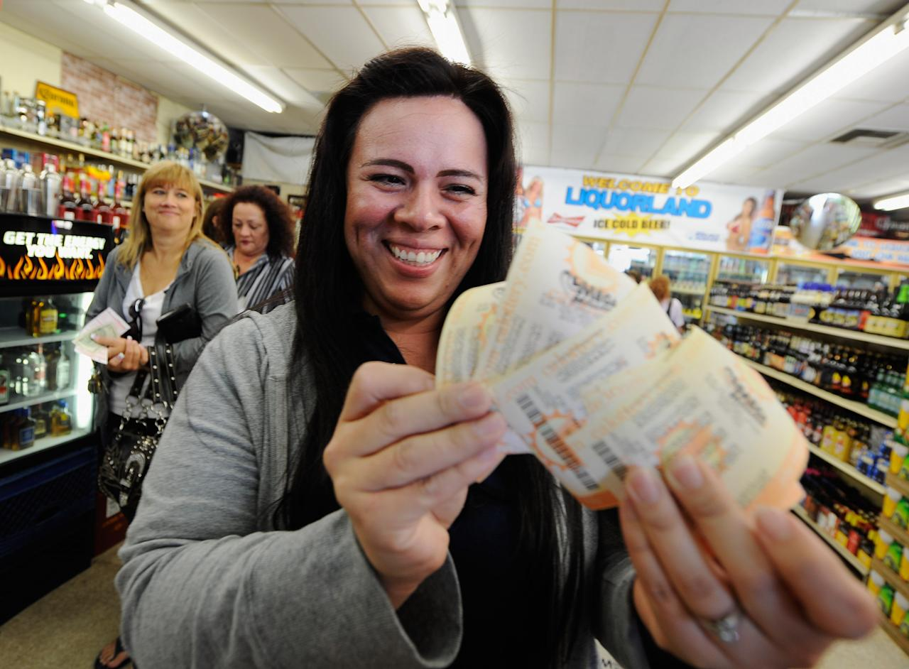Victoria Vazquez displays $280 worth of Mega Millions lottery tickets for her office pool that she purchased at Liquorland on March 30, 2012 in Covina, California The Mega Millions jackpot reached a high of $640 million before the drawing March 30. (Photo by Kevork Djansezian/Getty Images)