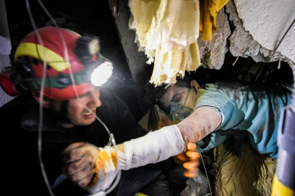 A firefighter tries to rescue a man stucked in the ruins of a collapsed building in Thumane, northwest of capital Tirana, after an earthquake hit Albania, on November 26, 2019. - Albanian rescuers scoured rubble into the night on Tuesday in search of survivors trapped in buildings toppled by the strongest earthquake in decades, with at least 20 lives lost and hundreds of people injured. The 6.4 magnitude quake struck before dawn at 3:54 am local time (0254 GMT), with an epicentre 34 kilometres (about 20 miles) northwest of the capital Tirana, according to the European-Mediterranean Seismological Centre. (Photo by Armend NIMANI / AFP) (Photo by ARMEND NIMANI/AFP via Getty Images)