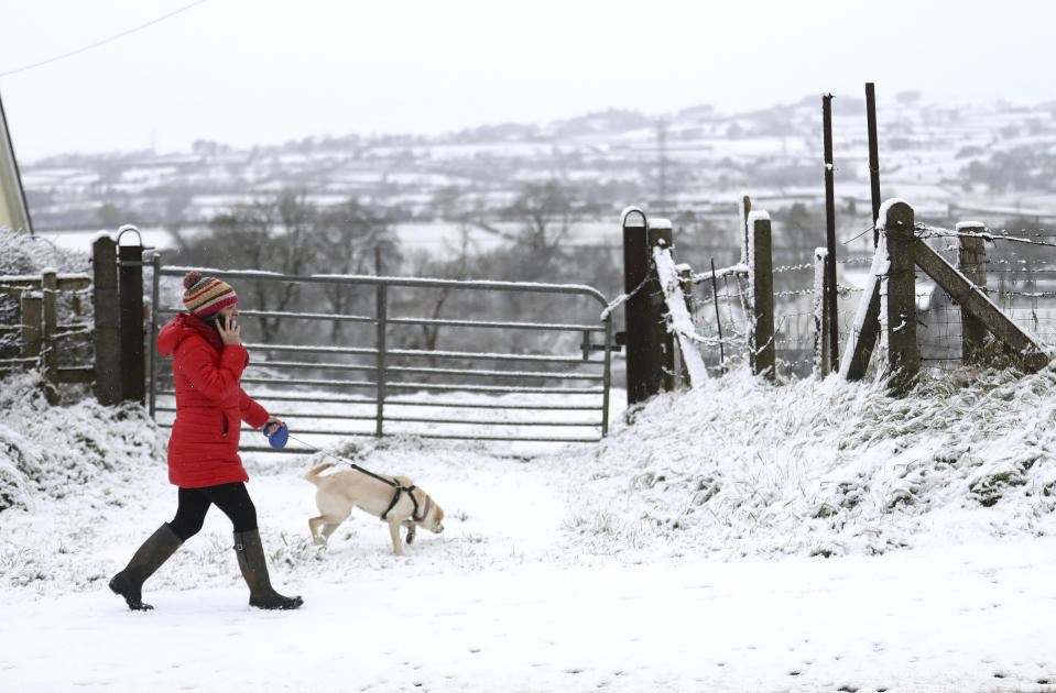 A woman takes her dog for a walk in the snow near Larne, Northern Ireland. (AP)
