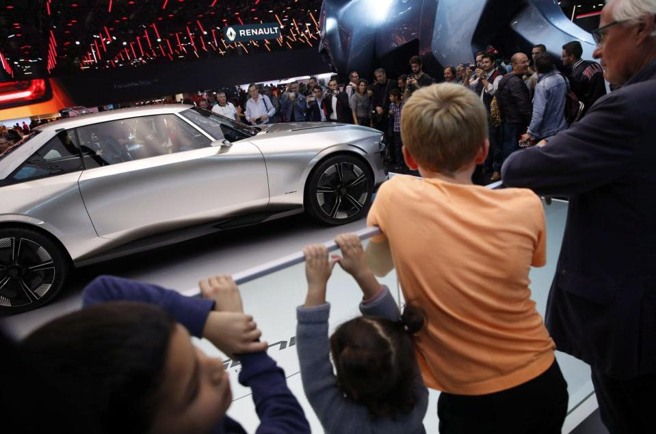 """<span class=""""caption"""">Visitors look at a Peugeot E Legend concept car on display at the Auto show in Paris, France, in 2018, where all-electric vehicles were among the stars of the show. </span> <span class=""""attribution""""><span class=""""source"""">(AP Photo/Christophe Ena) </span></span>"""