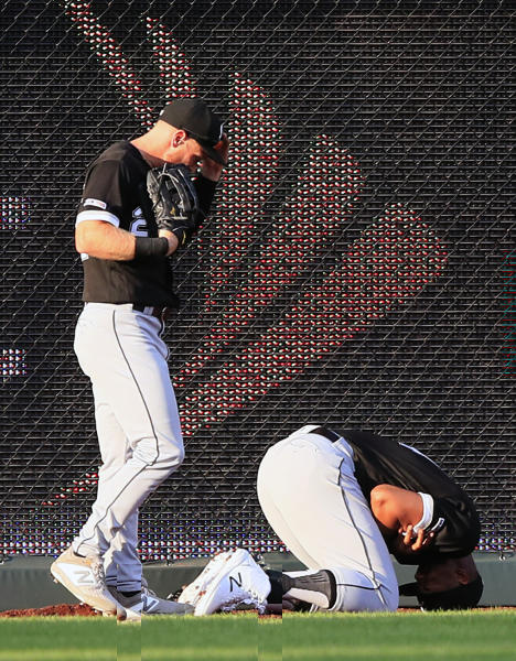 Chicago White Sox center fielder Charlie Tilson, left, looks to help left fielder Eloy Jimenez, after the pair collided catching a fly ball hit by Kansas City Royals' Whit Merrifield during the first inning of a baseball game at Kauffman Stadium in Kansas City, Mo., Tuesday, July 16, 2019. Jimenez was injured on the play. (AP Photo/Orlin Wagner)