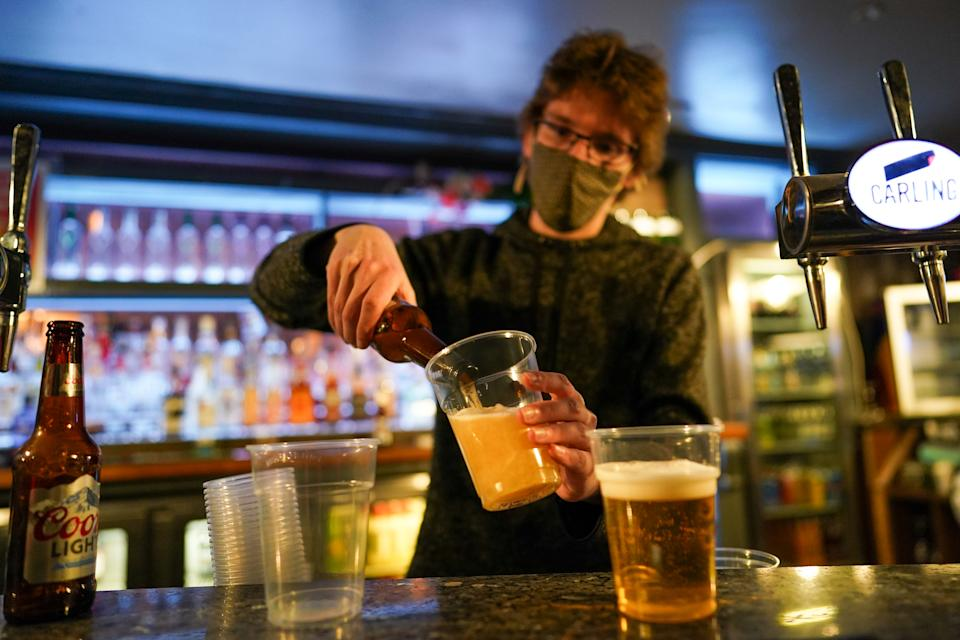 NEWCASTLE UPON TYNE, ENGLAND - APRIL 12: A member of the bar staff pours drinks in the Switch bar as it opens following the easing of lockdown measures on April 12, 2021 in Newcastle Upon Tyne, England. England has taken a significant step in easing its lockdown restrictions, with non-essential retail, beauty services, gyms and outdoor entertainment venues among the businesses given the green light to re-open with coronavirus precautions in place. Pubs and restaurants are also allowed open their outdoor areas, with no requirements for patrons to order food when buying alcoholic drinks. (Photo by Ian Forsyth/Getty Images)