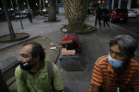 A sex worker naps on a bench as she waits for clients outside the Revolution subway station, in Mexico City, Saturday, March 13, 2021. Despite the common perception that sex work equals easy money, many of the longtime sex workers struggle to stay housed and to afford enough to eat, particularly since profit margins have plummeted amid the coronavirus pandemic, with more competition, fewer clients, and increased hotel prices. (AP Photo/Rebecca Blackwell)