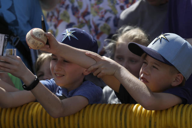 Young Tampa Bay Rays fans reach for autographs during spring training baseball camp Monday, Feb. 17, 2020, in Port Charlotte, Fla. (AP Photo/John Bazemore)