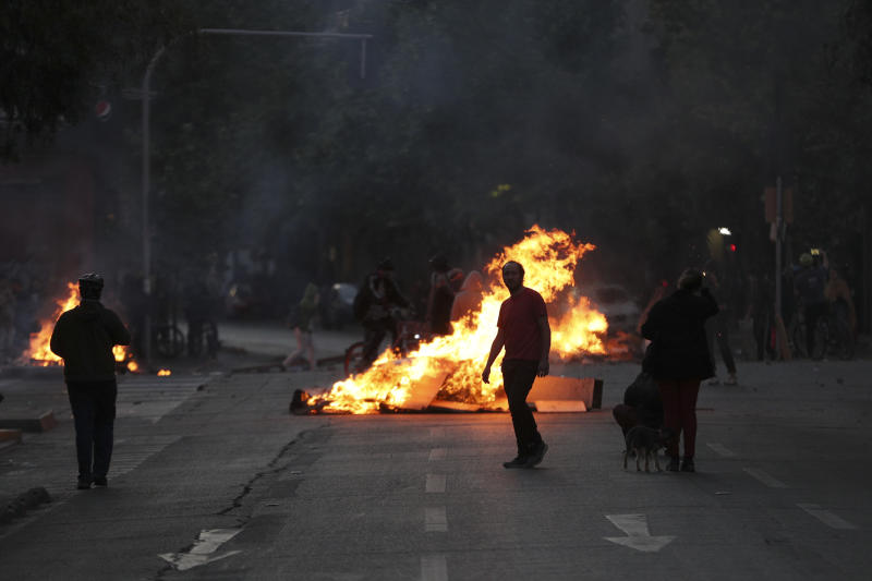 Protesters block a street with burning garbage and violate a curfew in downtown Santiago, Chile, Sunday, Oct. 20, 2019. Protests in the country have spilled over into a new day, even after President Sebastian Pinera cancelled the subway fare hike that prompted massive and violent demonstrations. (Photo: Esteban Felix/AP)