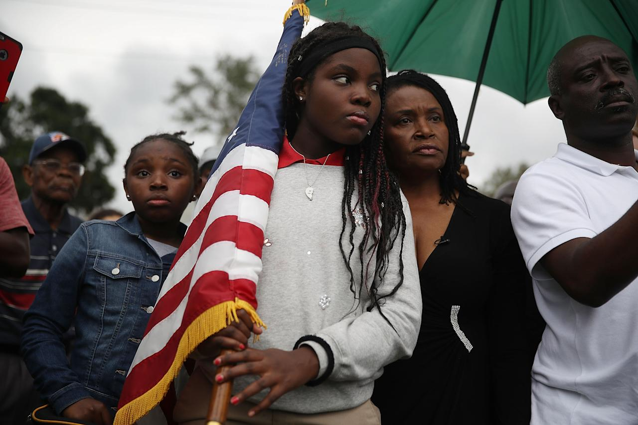 <p>Erika Rigaud,15, holds an American flag as she joins with others to mark the 8th anniversary of the massive earthquake in Haiti and to condemn President Donald Trump's reported statement about immigrants from Haiti, Africa and El Salvador on Jan. 12, 2018 in Miami, Fla. (Photo: Joe Raedle/Getty Images) </p>