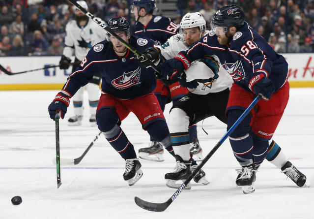 Columbus Blue Jackets' Pierre-Luc Dubois, left, David Savard, right, and San Jose Sharks' Kevin Labanc skate after a loose puck during the first period of an NHL hockey game Saturday, Jan. 4, 2020, in Columbus, Ohio. (AP Photo/Jay LaPrete)