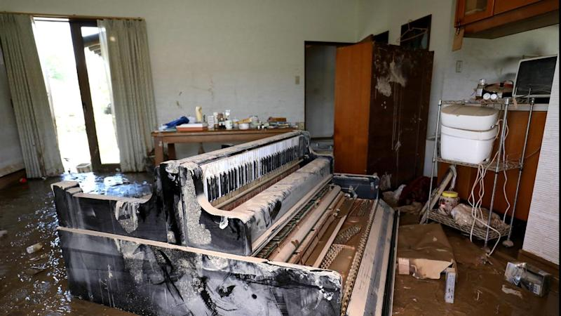 An upright piano is tipped over and buried in mud inside a flood-hit house in Japan