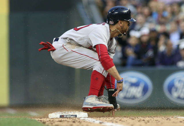 Boston Red Sox's Mookie Betts, left, hops over first base as he raced back to the base following a fly-out by Andrew Benintendi during the fifth inning of a baseball game against the Minnesota Twins on Tuesday, June 19, 2018, in Minneapolis. (AP Photo/Jim Mone)