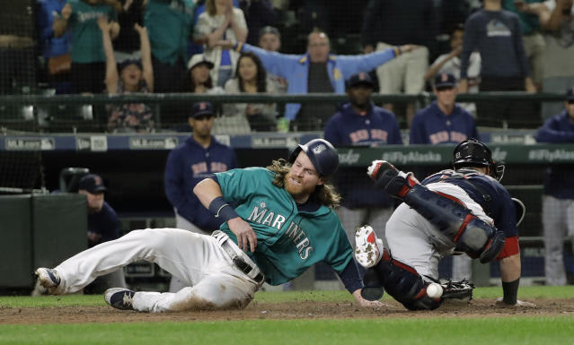 Seattle Mariners' Ben Gamel, left, scores as Boston Red Sox catcher Sandy Leon can't hold on to the ball during the eighth inning of a baseball game Friday, June 15, 2018, in Seattle. Gamel scored on a go-ahead two-run double by Denard Span. The Mariners won 7-6. (AP Photo/Ted S. Warren)