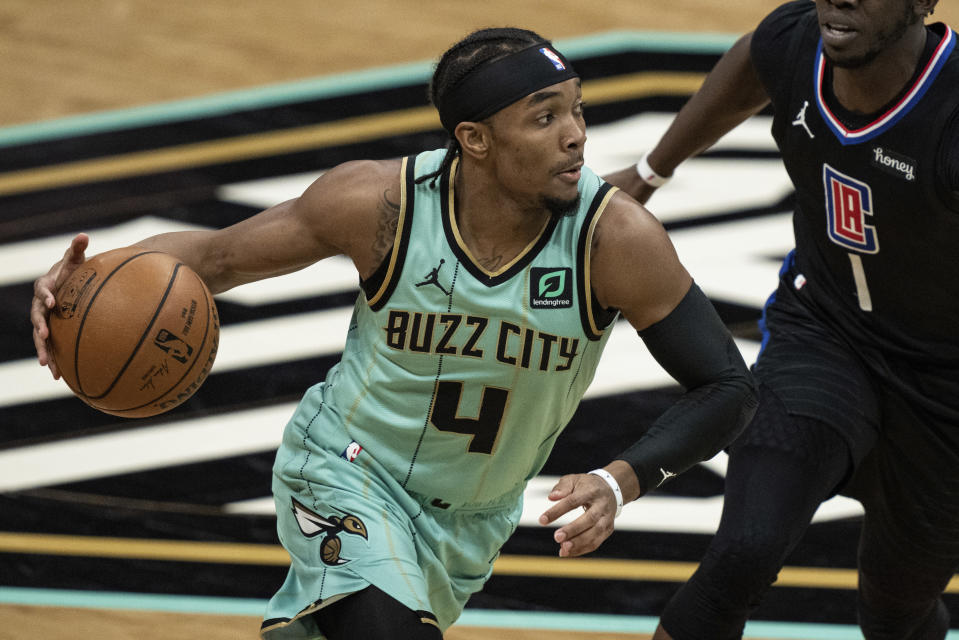 Charlotte Hornets guard Devonte' Graham (4) brings the ball up court while guarded by Los Angeles Clippers guard Reggie Jackson (1) during the second half of an NBA basketball game in Charlotte, N.C., Thursday, May 13, 2021. (AP Photo/Jacob Kupferman)