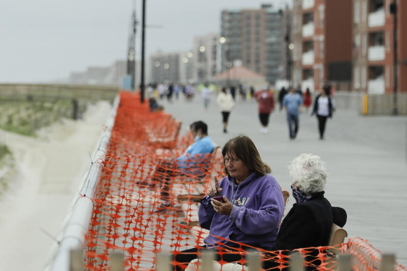 People engage in social distancing on the boardwalk during the coronavirus pandemic Friday, May 22, 2020, in Long Beach, N.Y. (AP Photo/Frank Franklin II)