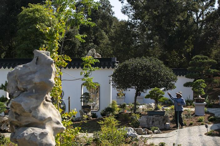 "A worker waters outside at the expansion of the Huntington's Chinese Garden, which opens Friday. <span class=""copyright"">(Josie Norris/Los Angeles Times)</span>"