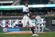 Minnesota Twins' Byron Buxton, left, jogs home to tie the baseball game on a single by Jorge Polanco off Toronto Blue Jays pitcher Steven Matz, center right, in the third inning of a baseball game, Thursday, Sept. 23, 2021, in Minneapolis. (AP Photo/Jim Mone)
