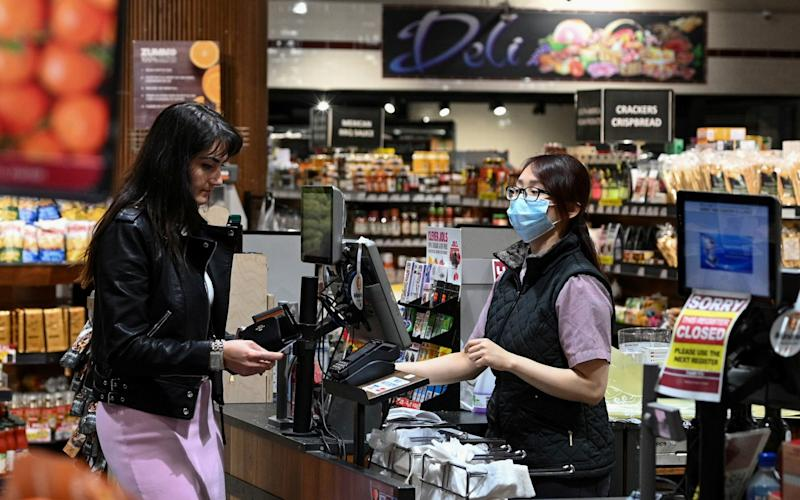 An employee wears a protective face mask while ringing up a customer at a specialty grocery store in Sydney -  Loren Elliott/Reuters