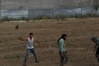Protestors hurl stones at Israeli troops near the fence of Gaza Strip border with Israel, during a protest marking the anniversary of a 1969 arson attack at Jerusalem's Al-Aqsa mosque by an Australian tourist later found to be mentally ill, east of Gaza City, Saturday, Aug. 21, 2021. (AP Photo/Adel Hana)
