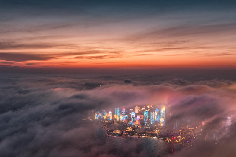 """FILE - In this April 20, 2018, file aerial photo released by China's Xinhua News Agency, advection fog drifts across skyscrapers on the waterfront in Qingdao in eastern China's Shandong Province. Chinese leaders have long been sensitive about their communist country's international image. Now, they are battling back, investing in diplomacy and a courtship of hearts and minds, just as the United States digs in on the Trump administration's """"America First"""" mindset. (Lu Hui/Xinhua via AP, File)"""