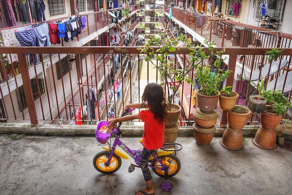 A girl rides a bicycle in the corridor of a low-cost flat in Kuala Lumpur September 29, 2019. — Picture by Ahmad Zamzahuri