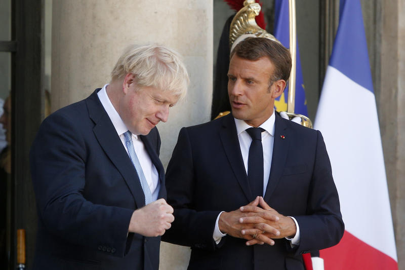 French President Emmanuel Macron, right, and Britain's Prime Minister Boris Johnson leave after their talks at the Elysee Palace, Thursday, Aug. 22, 2019 in Paris. Boris Johnson traveled to Berlin Wednesday to meet with Chancellor Angela Merkel before heading to Paris to meet with French President Emmanuel Macron. (AP Photo/Michel Spingler)