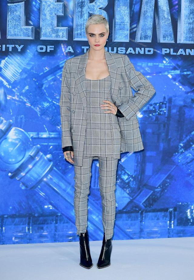 <p>Delevingne went down the masculine route, wearing a checked three-piece suit by Alexander Wang. Studded black boots finished off the striking ensemble. (Photo: PA) </p>