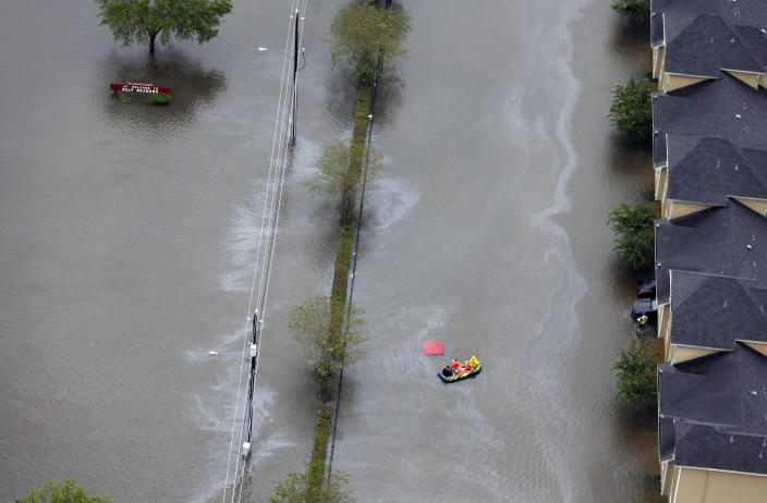 <p>A boat navigates through floodwaters from Tropical Storm Harvey on Tuesday, Aug. 29, 2017, in Houston. With its flood defenses strained, the crippled city of Houston anxiously watched dams and levees Tuesday to see if they would hold until the rain stops, and meteorologists offered the first reason for hope — a forecast with less than an inch of rain and even a chance for sunshine. (Photo: David J. Phillip/AP) </p>