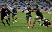 Australia's Noah Lolesio, centre, runs past New Zealand's Richie Mo'unga, right, and Aaron Smith left, to score his team's first try during the Bledisloe rugby test between the All Blacks and the Wallabies at Stadium Australia, Sydney, Australia, Saturday, Oct. 31, 2020. (AP Photo/Rick Rycroft)