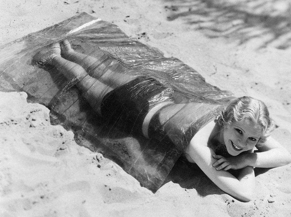 <p><em>Midnight Mystery</em> star June Clyde soaks up the sun underneath a cellophane blanket in 1932.</p>