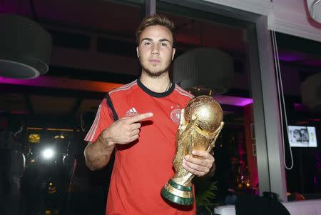 Germany's Mario Goetze poses with the World Cup trophy during the DFB-WM gala party in Rio de Janeiro