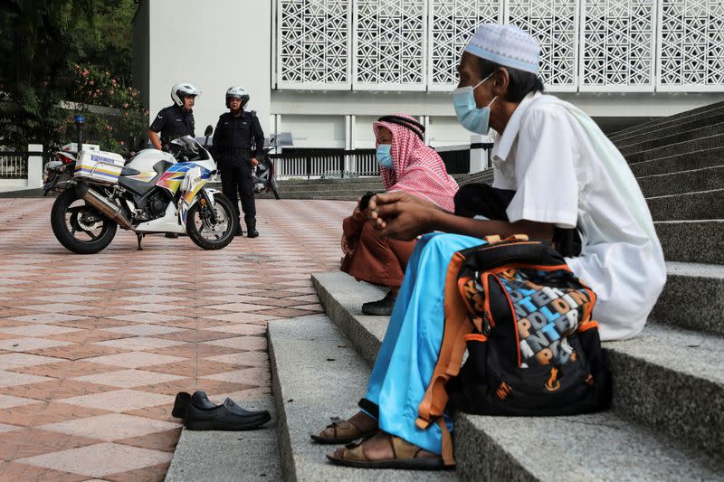 Police officers stand guard outside the closed National Mosque during Eid al-Fitr, the Muslim festival marking the end the holy fasting month of Ramadan, amid the coronavirus disease (COVID-19) outbreak in Kuala Lumpur