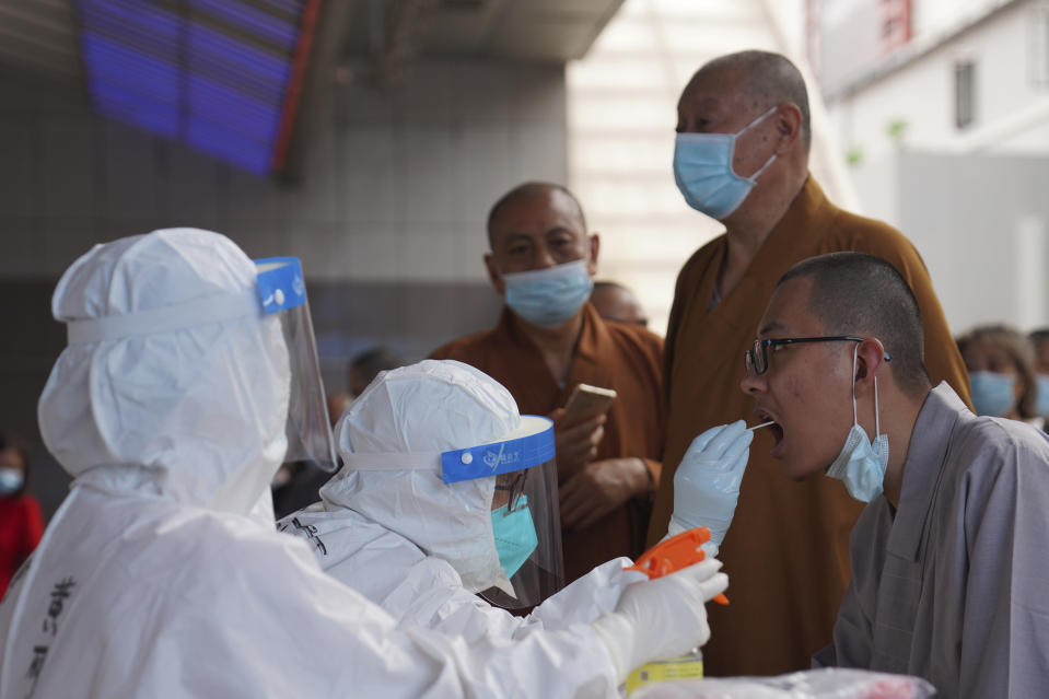 Monks get tested for the coronavirus in a district in Guangzhou in southern China's Guangdong province on Sunday, May 30, 2021. The southern Chinese city of Guangzhou shut down a neighborhood and ordered residents to stay home Saturday to be tested for the coronavirus following an upsurge in infections that has rattled authorities. (AP Photo)