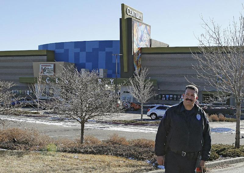 """Aurora Police Officer Mike Moore guards the entrance to the Century theater in Aurora, Colo., on Thursday, Jan. 17, 2013. The Colorado movie theater where a gunman killed 12 people and wounded dozens of others reopens Thursday with a private ceremony for victims, first responders and officials.   Theater owner Cinemark plans to temporarily reopen the entire 16-screen complex in Aurora to the public on Friday, then permanently on Jan. 25. Aurora's mayor, Steve Hogan, has said residents overwhelmingly support reclaiming what he calls """"an important venue for Aurora.""""  (AP Photo/Ed Andrieski)"""