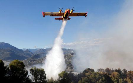 A Canadair firefighting aircraft drops water on a wildfire which burns a forest in Carros, near Nice, France, July 24, 2017. REUTERS/Eric Gaillard